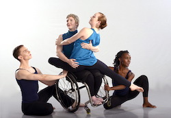 Laurel Lawson balances in a side tilt, holding a petite woman on her lap, both smiling. Two dancers wrap around them on the floor. Photo by Neil Dent, courtesy of Full Radius Dance.