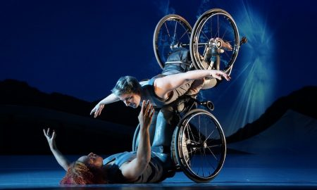 Laurel Lawson as Venus is flying in the air with arms spread wide, wheels spinning, and supported by Alice Sheppard as Andromeda who is lifting from the ground below. They are making eye contact and smiling. Photo by Jay Newman / BRITT Festival.