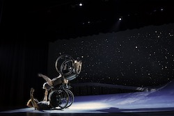 Two dancers in a lift; one balances with arms spread wide, wheelchair wheels spinning, as the other supports her with open arms extended. A starry sky fills the background. Alice Sheppard and Laurel Lawson of Kinetic Light. Photo by BRITT/Jay Newman.