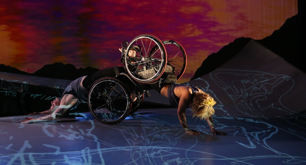Two dancers, both in wheelchairs; one crawls forward and the other arches her back as she is dragged along the floor. A sunset appears behind them. Alice Sheppard and Laurel Lawson of Kinetic Light. Photo by MANCC/Chris Cameron.